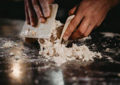 Mani che impastano la pasta fatta a mano