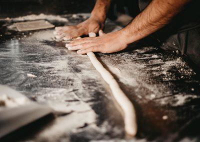 Mani che stendono l'impasto per la pasta fatta a mano