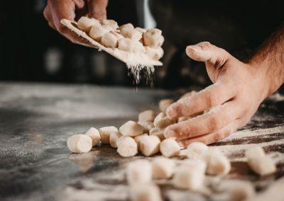 Mani che infarinano gli gnocchi fatti a mano di Ristorante Mangio Roma