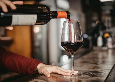 Una mano che versa un vino rosso nel calice di Ristorante Mangio Roma
